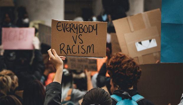"""Ein Bild einer Demonstration mit Plakaten. Der Schriftzug """"everybody vs. racism"""" ist zu lesen."""