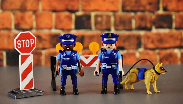 Zwei Playmobil Figuren in Polizeiuniform, davon eine person of colour. rechts daneben steht ein angeleinter Playmobil-Polizeihund.