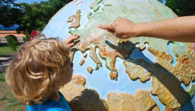 Ein großer Globus mit Fokus auf Europa, ein Kind steht interessiert vor dem Globus und eine Hand zeigt auf Europa.