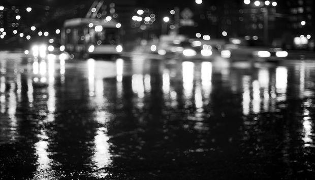 Eine Nasse Straße von unten auf den Verkehr fotgrafiert. Die Lichter spiegeln sich auf der nassen Fahrbahn.