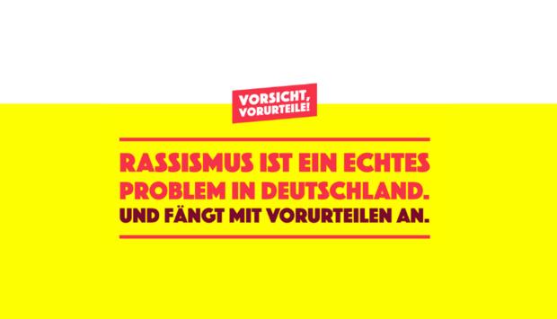 Ein Bild der Plakatkampagne Vorsicht Vorurteil! Darauf steht vor einem gelben Hintergrund mit roter Schrift: Rassismus ist ein echtes Problem in Deutschland und fängt mit vorurteilen an.