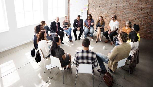 Eine Gruppe von Menschen sitzt in einem Stuhlkreis bei einem Workshop.