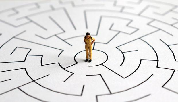 Eine Miniaturfigur steht auf einem Blatt Papier. Darauf ist ein Labyrinth eingezeichnet. Die Miniaturfigur steht ratlos in der Mitte.