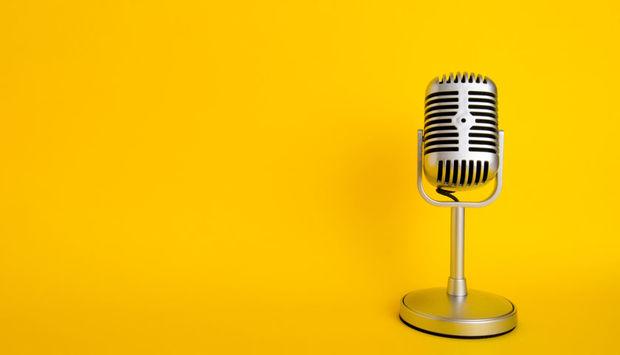 Ein altes metallenes Mikrofon steht vor einem gelben Hintergrund.