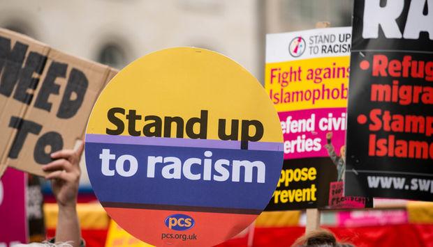 Ein Foto von einer Demonstration, viele Transparente, im Vordergrund ein Schild mit den Worten: Stand up to racism