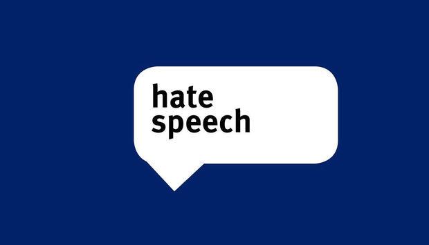 Abgebildet ist eine weiße Sprechblase auf dunkelblauem Grund mit der Aufschrift hate speech.