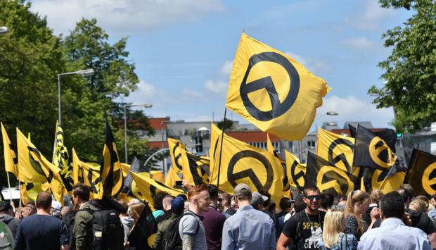 Ein Demonstrationszug von der extrem rechten Identitären Bewegung mit Flaggen mit dem Logo der IB in gelb mit einem Lambda darauf.