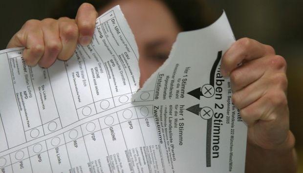 Eine Frau zerreißt mit beiden Händen einen Stimmzettel einer Landtagswahl.