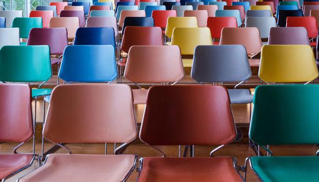 Ein Foto von einem vielen leeren, bunten Stühlen in Kinobestuhlung.