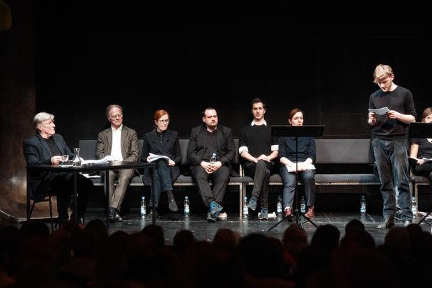 Eine Gruppe von Menschen sitzt auf einer Bühne, ein Mann steht am Mikrofon und liest. Es ist ein Foto der Schauspieler der Lesung.