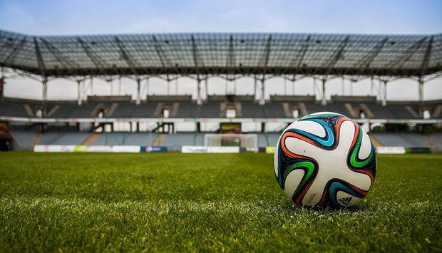 Ein Fußball liegt auf dem Rasen in einem großen Fußballstadion