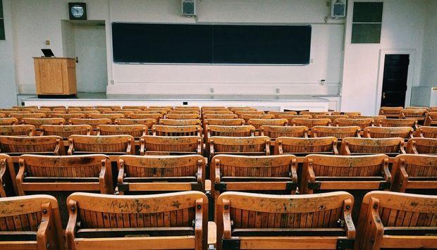 Ein Hörsaal mit leeren Sitzreihen und einer Tafel.