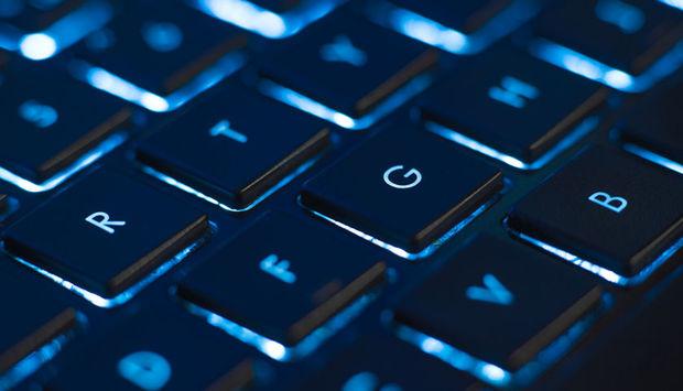 Ein Ausschnitt einer Laptoptastatur, die blau schimmert.