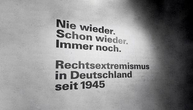 """Schräge schwarze Aufschrift """"Nie wieder. Schon wieder. Immer noch. Rechtsextremismus in Deutschland seit 1945""""mit Schattenwurf"""