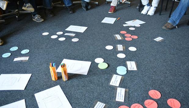 Man sieht dir Füße von Personen, die in einem Sitzkreis sitzen. In der Mitte auf dem Boden liegen Stifte, Papier und bunte Moderationskarten.