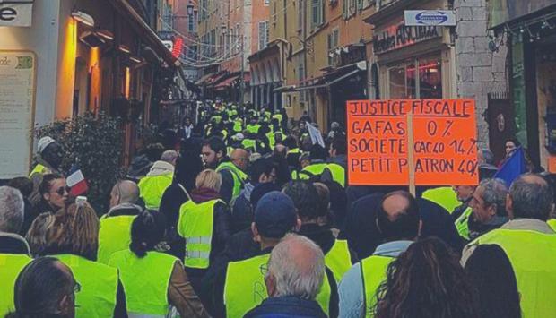 Ein Foto von einer Demonstration der Gelbwesten-Bewegung in Frankreich mit vielen Menschen mit gelben Warnwesten in einer engen Gasse udn einem Organgen Schid.