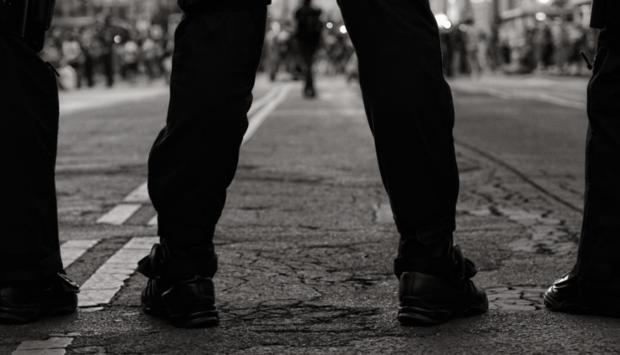 Ein Bild von einem breitbeinig stehenden Mann von hintern knieabwärts. Man sieht durch die BEine die Straße und es könnte eine Demonstration sein. Sinnbild für extreme Rechte und Männlichkeit.