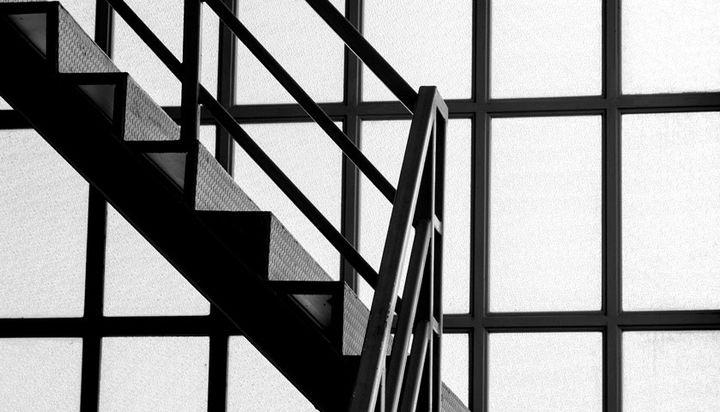 Ein schwarzweiß Foto eines modernen Treppenhauses ohne Menschen im bild.