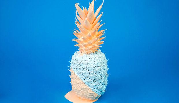 eine mit weißer und rosefarbener Farbe angestrichene Ananas vor blauem Hintergund