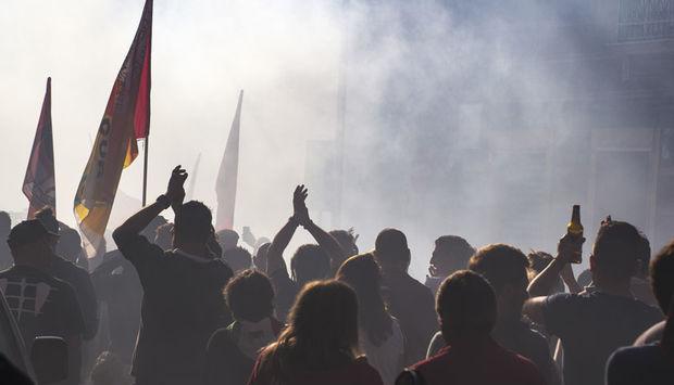 Ein Foto von einem Demonastrationszug mit vielen Menschen mit Fahnen in der Hand. Rauch umgiebt die Menschen.