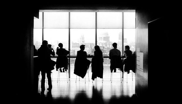 Sechs Personen sitzen auf Stühlen vor einer Glaswand und unterhalten sich. Das Bild ist in schwarz/weiß.