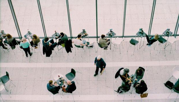 Aus der Vogelperspektive sieht man Tische und einige Menschen, die an den Tischen sitzen und eine Person, die durch den Raum geht. Oben im Bild ist eine Glaswand.