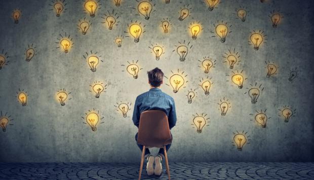 Ein Mann sitz mit dem Rücken zur Kamera auf einem Stuhl und blickt in Richtung einer Wand. Auf der Wand sind viele gezeichnete Glühbirnen.