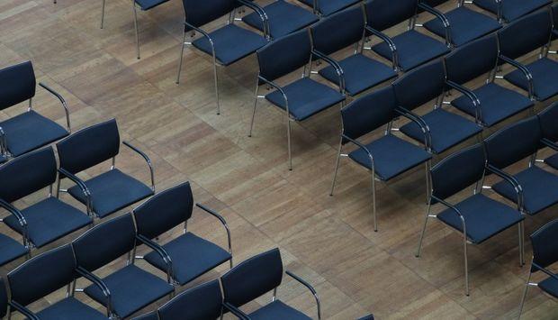 Ein Saal aus der Vogelperspektive fotografiert zeigt einen Gang zwischen zwei Sitzblöcken aus blauen Stühlen. Der Saal ist menschenleer.