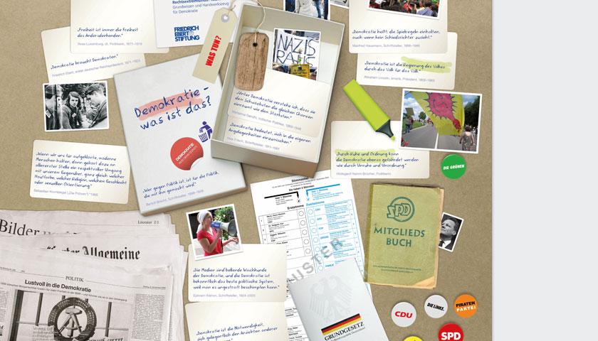 Zeigt einen Ausschnitt des Flyers mit weiteren Postkarten und Pins mit den Logos der Bundestagsparteien, welche auf einer braunen Pinnwand hängen.