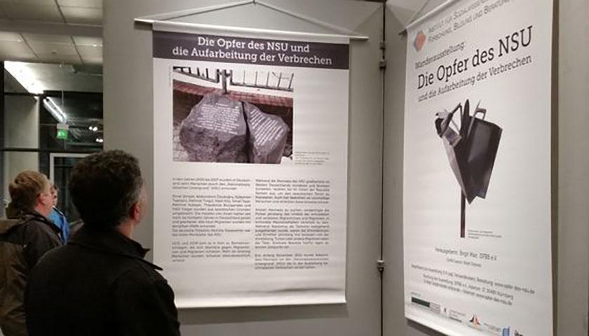 Das Bild zeigt einen Teil der aufgebauten Ausstellungen mit Personen, die sich die Schaubilder ansehen