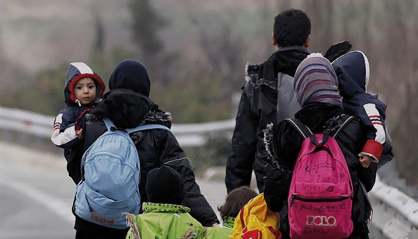 Das Bild zeigt von hinten eine Famile, die mit Gepäck eine Straße entlangläuft.