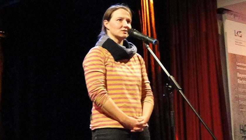 Abgebildet ist eine Frau auf einer Bühne, die in ein Mikrofon spricht.