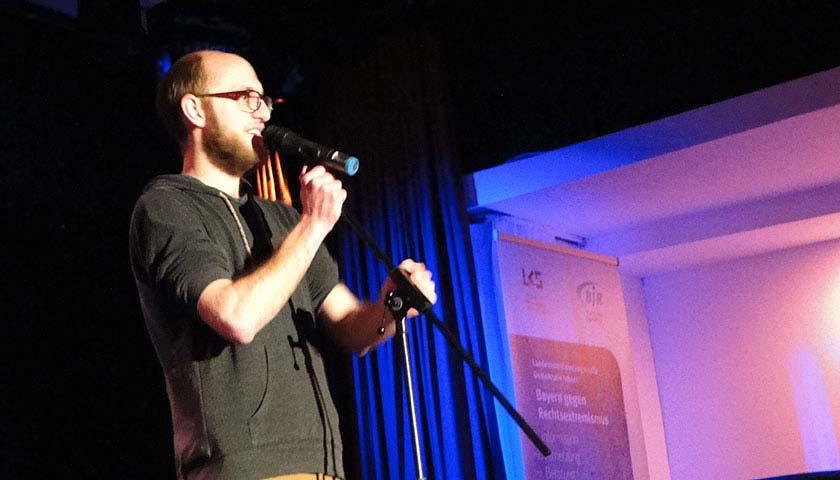 Abgebildet ist ein Mann auf einer Bühne, der in ein Mikrofon spricht.