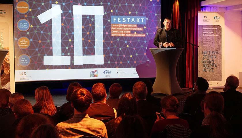 Abgebildet ist ein Foto von einem sitzenden Publikum. Auf der Bühne steht ein Mann an einem Pult und spricht in ein Mikrofon.