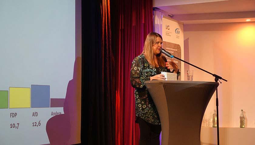 Abgebildet ist eine Frau an einem Podium, die in ein Mikrofon spricht.