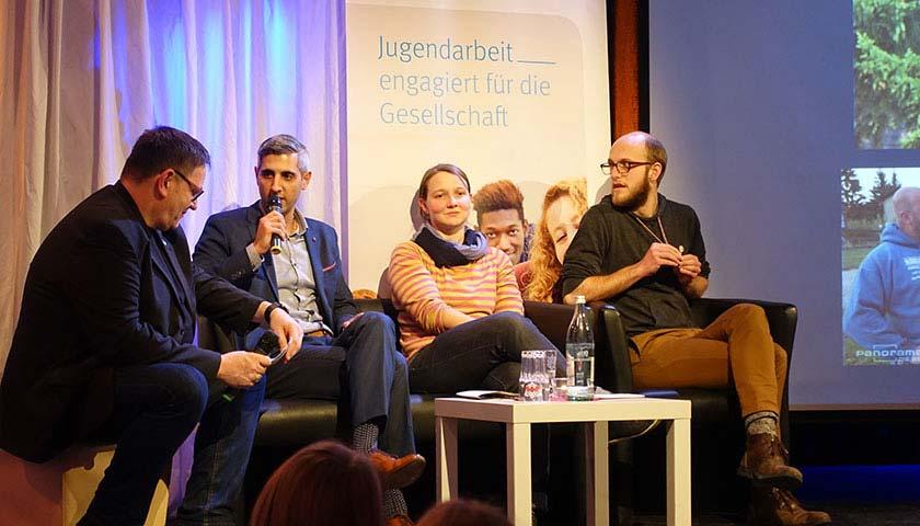 Abgebildet sind 4 Personen auf einem Podium, ein Mann hält ein Mikrofon.