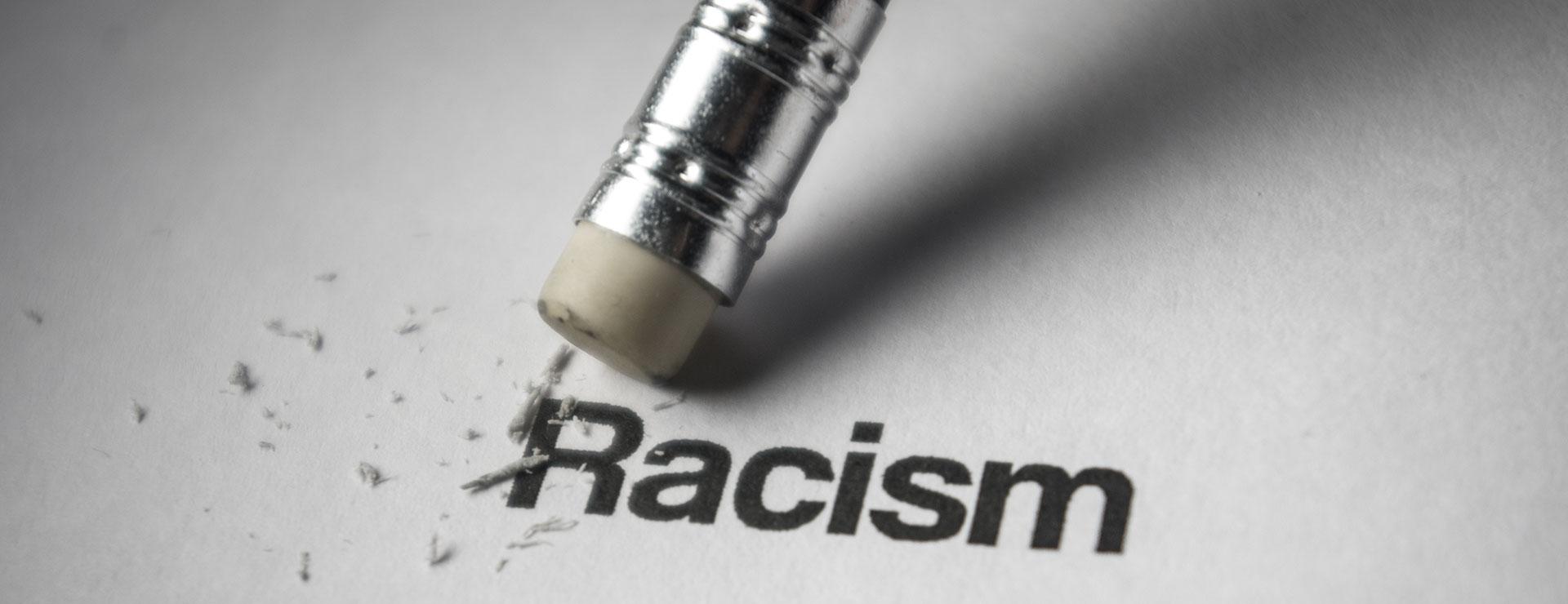 Das Bild zeigt ein Blatt Papier, auf dem das Wort Racism steht. Das Wort wird von einem Radiergummi ausradiert.