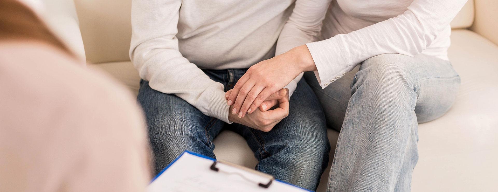 Das Bild zeigt eine Beratungssituation mit einem Elternpaar und einer Beraterperson. Das Elternpaar hält sich an den Händen.